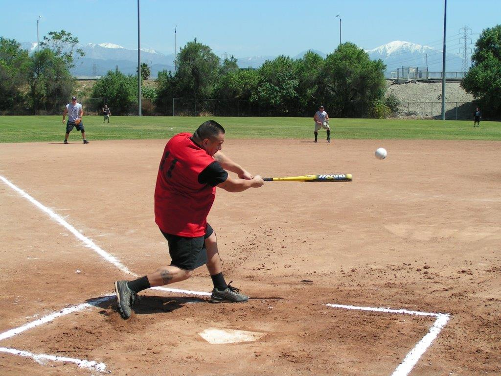 Adult man swinging a bat during a softball game
