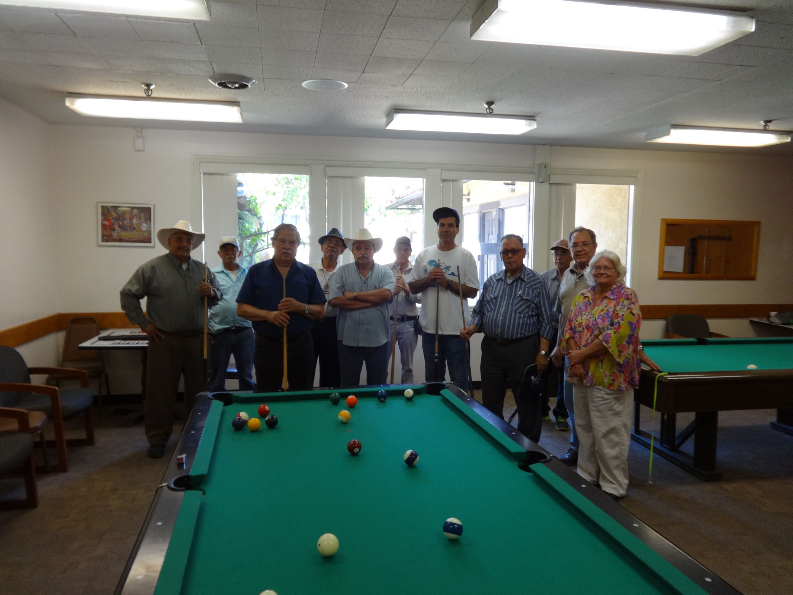 Group picture of older gentlemen by the billiards table